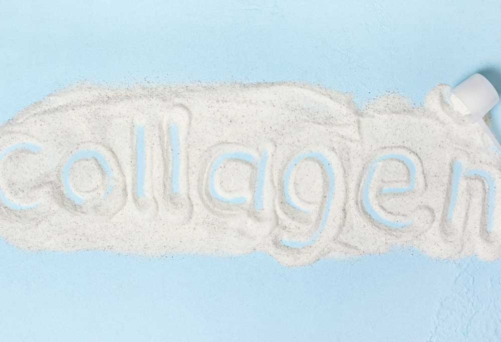 The word collagen spelled out in collagen powder on a blue background.