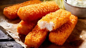 fish sticks on a piece of brown paper on a wooden table with tartar sauce in the background