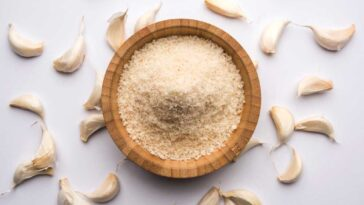 Garlic powder in a wooden bowl on a white background surrounded by garlic cloves