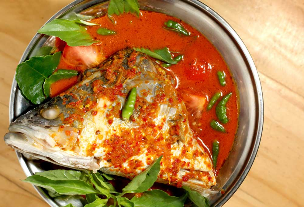 Fish head resting in a bowl of red broth with leafy greens