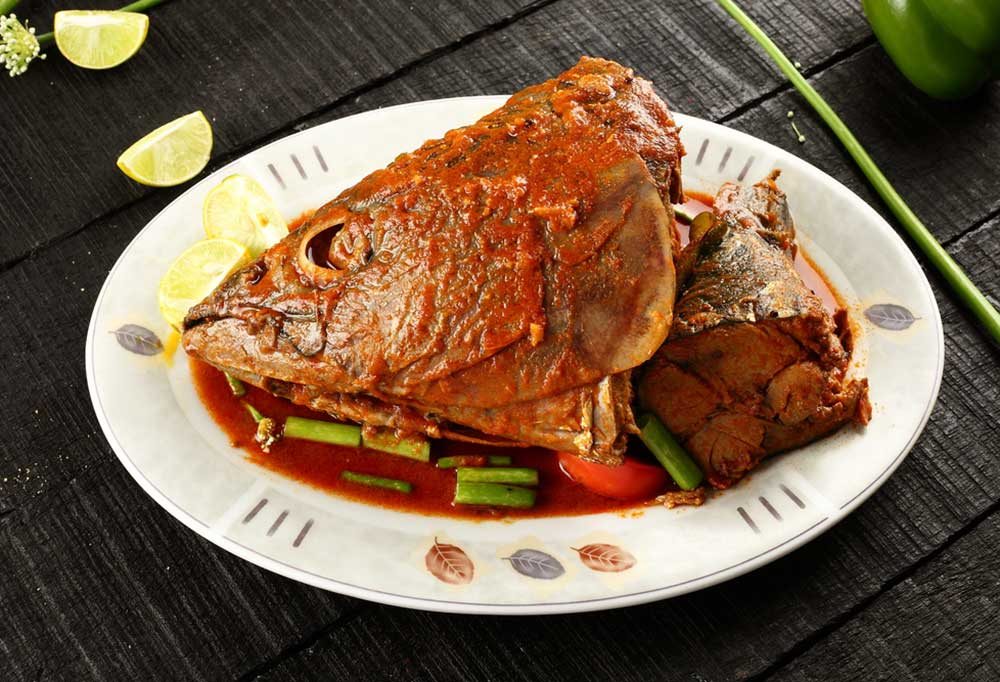 Fish head cooked in a red sauce on a white plate on a black table.