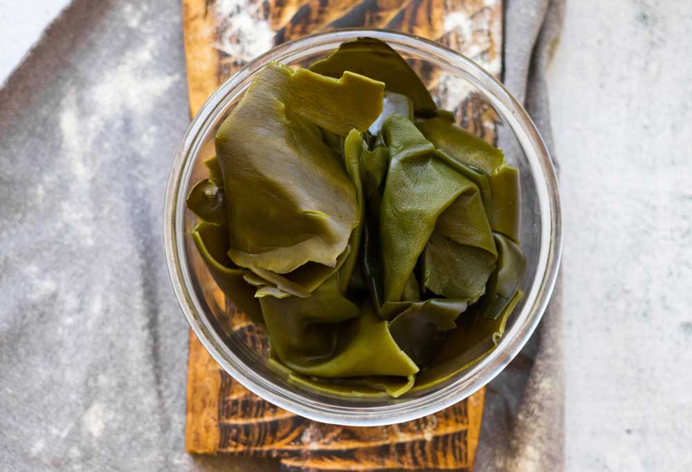 Kombu in a bowl sitting on a wooden plank