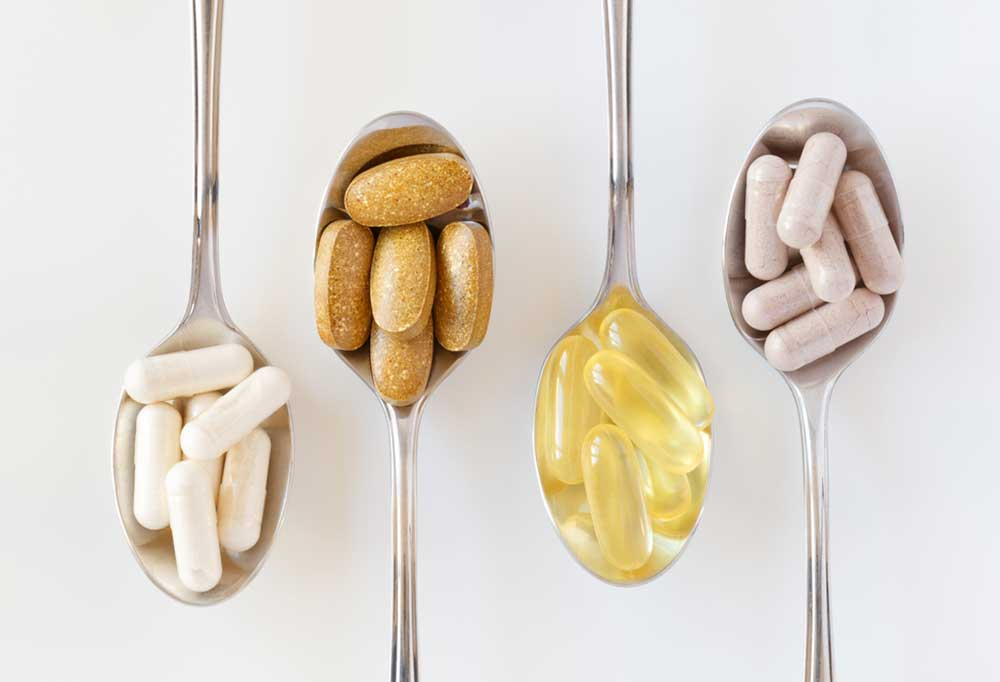 Vitamin pills on spoons isolated on a white background