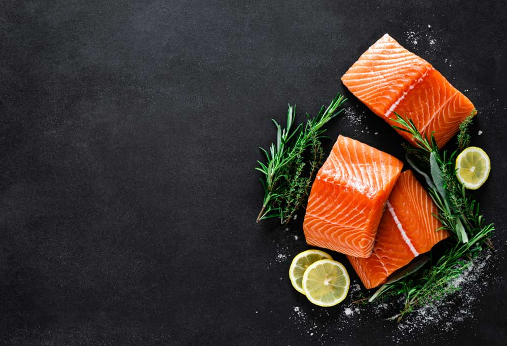 Salmon fillets on a black slate surrounded by sprigs of herbs, spices, and lemon slices