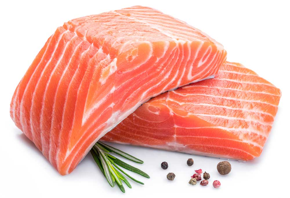 Salmon fillets and some herbs and spices on a white background
