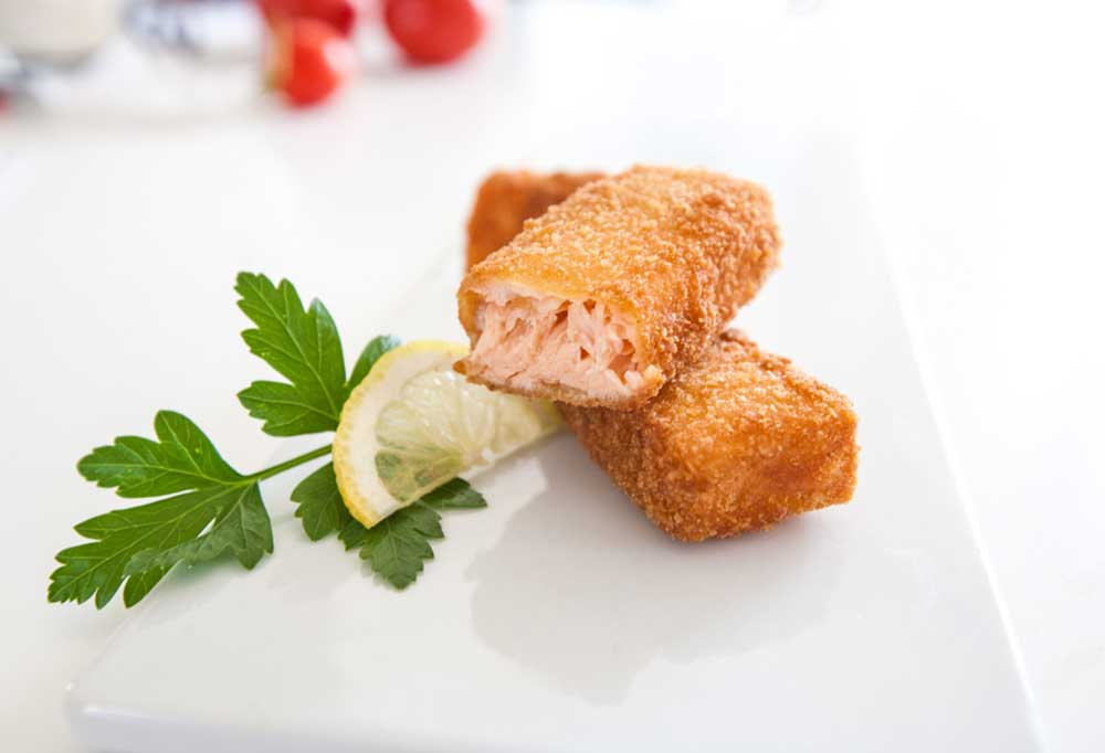 Fish stick made of salmon broken in half on a white plate with lemon wedge and parsley