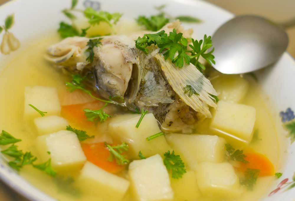 Fish head in a light yellowy broth with potato carrots and parsley