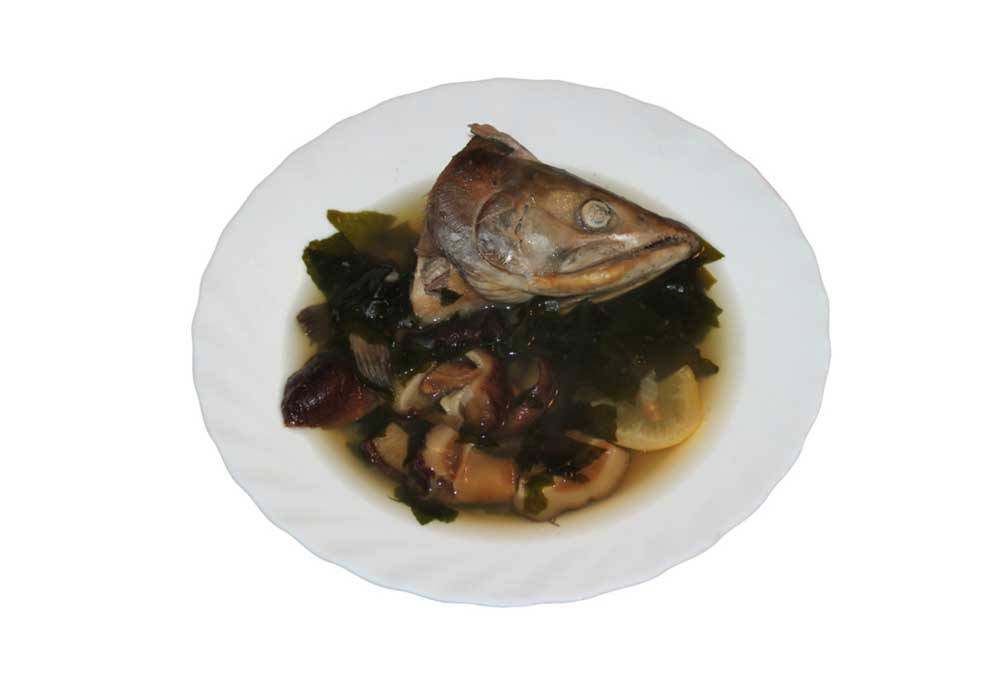 Salmon head in a broth with seaweed and fish pieces
