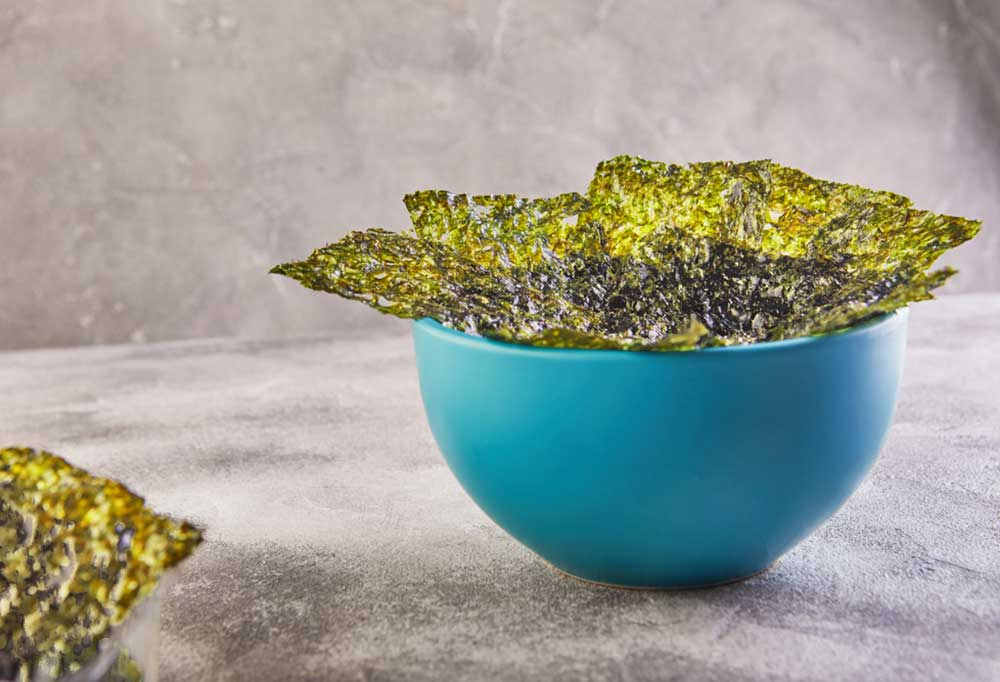 Nori sheets in a blue bowl on a marbled grey background