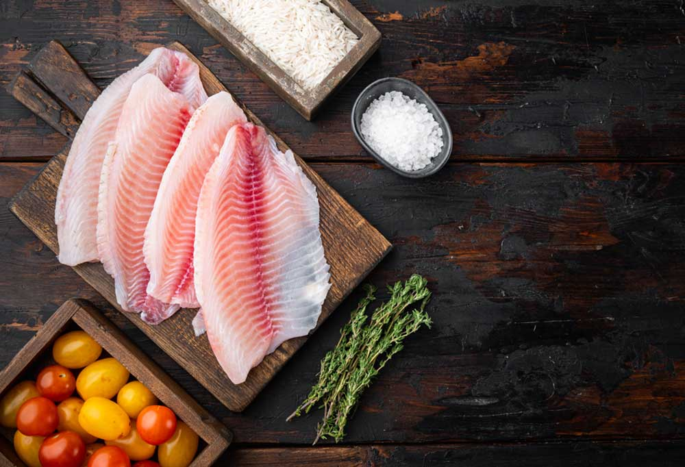 Tilapia filets on a wooden cutting board on a dark wood table