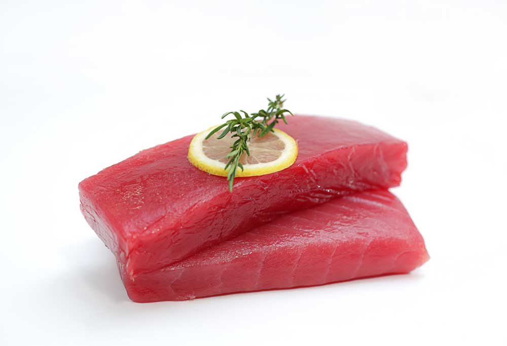 Raw tuna steaks with a slice of lemon and rosemary on top on a white background