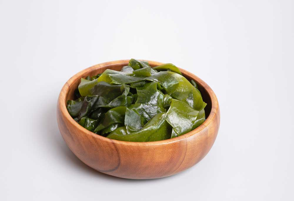 Wakame in a wooden bowl on a white background.