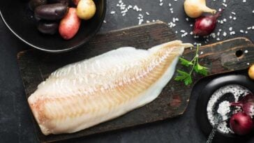 Cod fillet on a wooden cutting board surrounded by seasonings and vegetables on a slate counter top