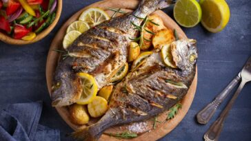 Grilled fish on a plate with garnish on a slate background